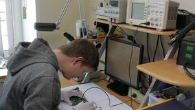 Mani di tecnologia professionale che riparano le componenti di piccolo computer sulla tavola del microscopio facendo uso del sald stock footage