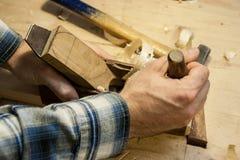 Mani di un artigiano su un vecchio aereo di falegnameria di modo immagini stock