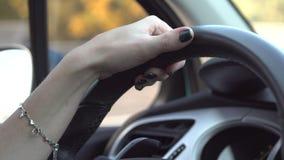 Mani di un autista della donna sul volante di un'automobile archivi video