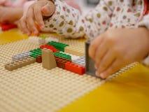 Mani di un bambino che gioca i mattoni di plastica di collegamento variopinti fotografia stock libera da diritti