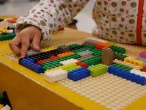 Mani di un bambino che gioca i mattoni di plastica di collegamento variopinti fotografia stock