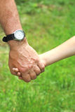 Mani di un genitore e di un bambino Immagini Stock