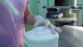 Mani di un infermiere che apre un barattolo con le strofinate sterili archivi video