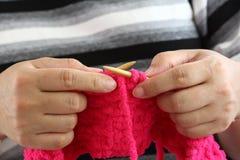 Mani di un lavoro a maglia della giovane donna Fotografia Stock