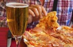Mani di un mangiatore di uomini la pizza italiana, un vetro dell'orso e K Immagini Stock