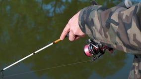 Mani di un pescatore con un primo piano disponibile della barretta di filatura stock footage