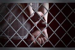 Mani di un prigioniero dietro le barre d'acciaio in una cella di prigione immagini stock libere da diritti