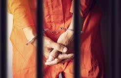 Mani di un prigioniero in manette dietro le barre di una prigione in vestiti arancio della tuta fotografia stock