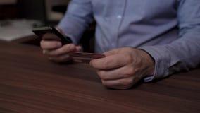 Mani di un telefono cellulare della tenuta dell'uomo d'affari e di una carta di credito Usa la sua carta di credito per pagare on video d archivio