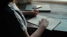 Mani di un tiraggio della giovane donna con una matita sulla fine della carta su archivi video