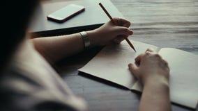 Mani di un tiraggio della giovane donna con una matita sulla fine della carta su stock footage