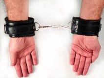 Mani di un uomo che indossano le manette di cuoio simili a pelliccia nere del giocattolo del sesso fotografie stock libere da diritti