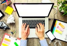Mani di un uomo che per mezzo del computer portatile con esposizione vuota Fotografia Stock
