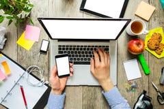 Mani di un uomo che per mezzo del computer portatile e dello smartphone Fotografia Stock Libera da Diritti