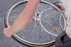 Mani di un uomo che ripara una ruota piana Fotografia Stock