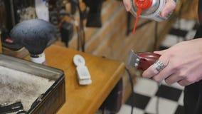Mani di un uomo con i tagliatori elettrici di un barbiere d'annata per la barba ed i capelli Barbiere di professione, parrucchier stock footage