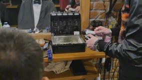 Mani di un uomo con i tagliatori elettrici di un barbiere d'annata per la barba ed i capelli Barbiere di professione, parrucchier video d archivio