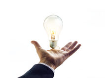 Mani di un uomo d'affari che raggiunge verso alla lampadina, concetto di affari Immagini Stock Libere da Diritti
