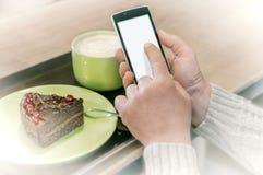 Mani di un uomo facendo uso di un dispositivo dello smartphone in caffè fotografia stock