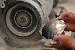 Mani di un uomo di Islander del cuoco che lucida la perla nera di Tahitian lei fotografie stock
