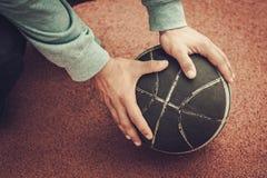 Mani di un uomo su una palla di pallacanestro Fotografia Stock Libera da Diritti