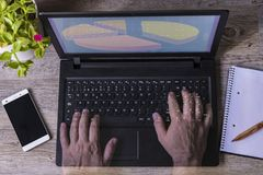 Mani di un uomo in tavola di legno della pianta del taccuino del telefono del computer fotografia stock libera da diritti