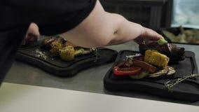 Mani di una cameriera di bar Take Wooden Boards della donna con carne Pronto-al forno stock footage