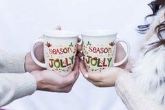 Mani di una coppia che tiene 2 tazze decorative di festa Immagine Stock