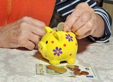 Mani di una donna anziana che tiene una moneta Immagini Stock Libere da Diritti