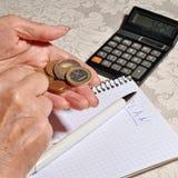 Mani di una donna anziana che tiene una moneta Fotografia Stock