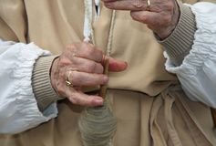 Mani di una donna anziana durante l'elaborazione del maglione della lana Fotografie Stock Libere da Diritti