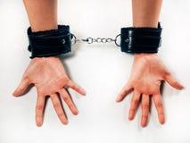 Mani di una donna che indossano un paio delle manette di cuoio simili a pelliccia nere del giocattolo del sesso fotografie stock libere da diritti