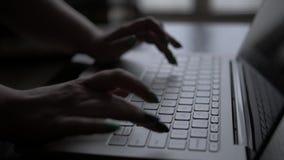 Mani di una donna che lavora ad un computer portatile nella sera, dalla finestra, primo piano video d archivio