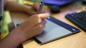 Mani di una donna che lavora con la compressa del disegno per un computer archivi video