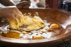Mani di una donna che mescolano gli ingredienti come le uova crude, farina, polvere B fotografia stock libera da diritti