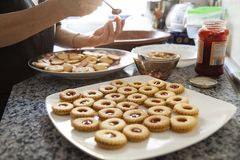 Mani di una donna che mescolano gli ingredienti come le uova crude, farina, polvere burro e zucchero bianco su una grande pasta d immagine stock libera da diritti