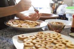 Mani di una donna che mescolano gli ingredienti come le uova crude, farina, polvere burro e zucchero bianco su una grande pasta d immagine stock