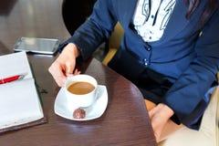Mani di una donna che si siede ad una tavola che tiene una tazza di caffè Fotografia Stock