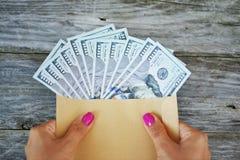 Mani di una donna che tiene una busta in pieno delle banconote dei dollari americani immagine stock libera da diritti
