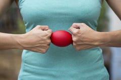 Mani di una donna che tiene una palla di sforzo Fotografie Stock