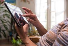 Mani di una donna senior che per mezzo di una compressa Immagine Stock Libera da Diritti