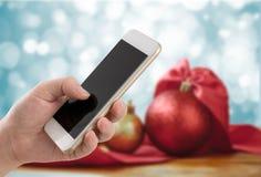 Mani di una giovane donna che per mezzo del telefono cellulare con il backgro di Natale Immagini Stock