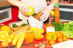 Mani di una giovane donna che prepara la scatola della refezione Immagine Stock