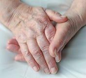 Mani di una persona anziana Fotografie Stock