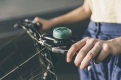 Mani di una ragazza sul vecchio manubrio d'annata della bicicletta Immagine Stock
