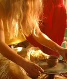 Mani di una ragazza sulla ruota del vasaio Fotografia Stock
