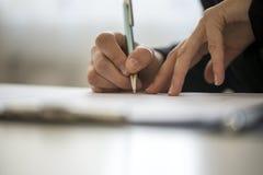 Mani di una scrittura della persona su un blocco note Fotografie Stock