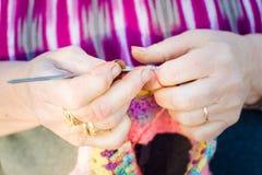 Mani di una signora anziana che tricotta sui ferri da maglia, facendo uso della lana variopinta immagini stock libere da diritti