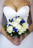 Mani di una sposa con un mazzo Immagini Stock