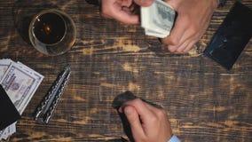 Mani di vista superiore dell'uomo d'affari che mettono un pacco di valuta estera sulla tavola Armi maschii del trafficante di dro video d archivio